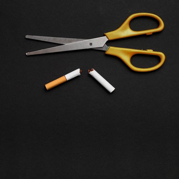 はさみと黒の背景上の壊れたタバコの立面図 無料写真