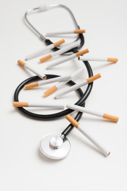 タバコと白い背景の上の聴診器のクローズアップ 無料写真