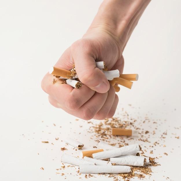 白い背景の上のタバコのしわ男の拳 無料写真