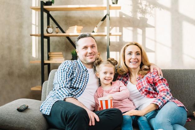 幸せな家族の自宅でソファの上のポップコーンを食べる娘と一緒にテレビを見ています。 無料写真