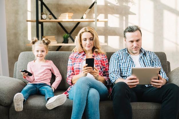娘がテレビを見ながらデジタルタブレットと携帯電話を使用している親 無料写真