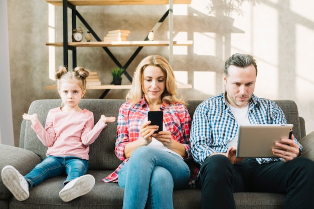 Сердитая дочь сидя на кресле с ее матерью и отцом используя цифровую таблетку; мобильный телефон дома Бесплатные Фотографии