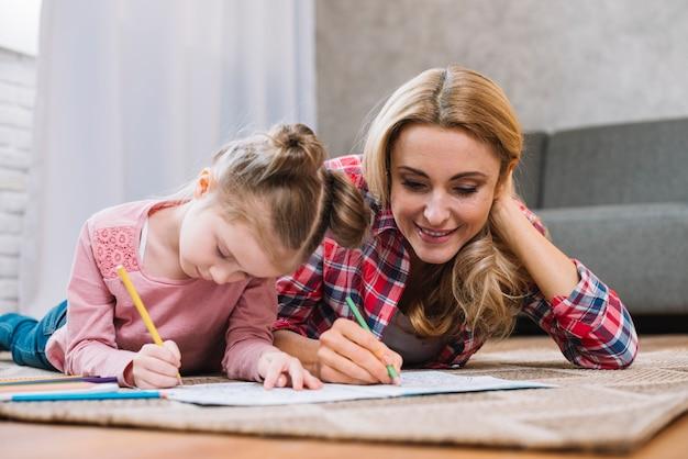 美しい母親と娘が家で本に一緒に描いています。 無料写真