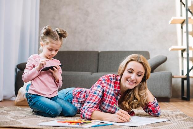 携帯電話を使用して彼女の娘と一緒に本を描く母親を笑顔 無料写真