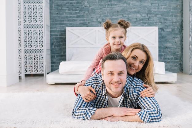 寝室でお互いに横になっている笑顔の家族の肖像画 無料写真