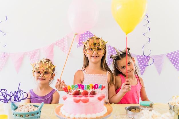 誕生日パーティーで楽しんでいる風船を保持しているアイマスクを着ている女性の友達に笑顔 無料写真