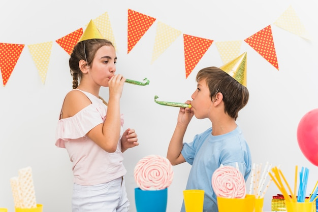男の子と女の子の誕生日パーティー中にパーティーホーンを吹く 無料写真