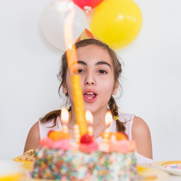 パーティーでおいしい誕生日ケーキのろうそくを吹きかわいい女の子のクローズアップ 無料写真