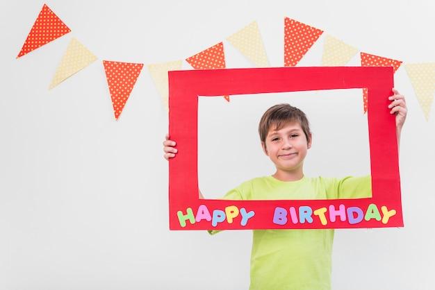 Улыбающийся мальчик держит рамку с днем рождения рамку против стены, украшенной овсянкой Бесплатные Фотографии