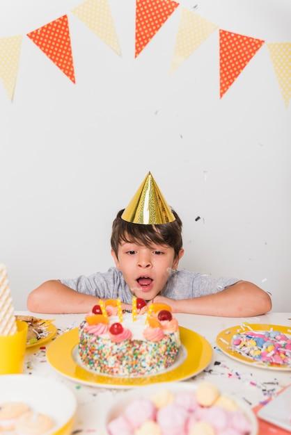 誕生日の男の子がケーキの上のろうそくを吹き 無料写真