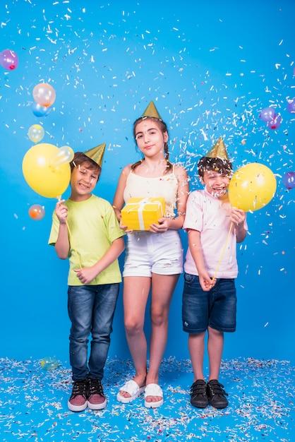 友達に笑顔でプレゼント付きの誕生日パーティーを祝います。風船と青い背景上の紙吹雪 無料写真