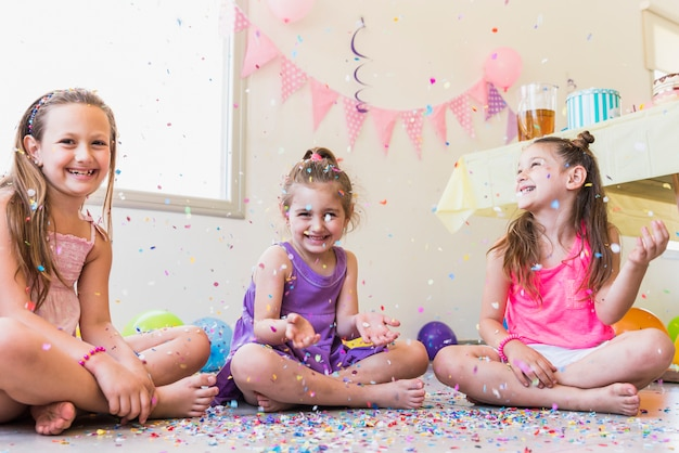 誕生日パーティーの間に紙吹雪で遊んで幸せな女の子のグループ 無料写真