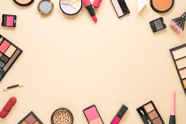 Различные виды косметики разбросаны по бежевому столу Бесплатные Фотографии