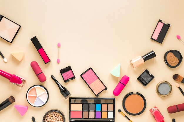 ベージュのテーブルに散らばって様々な化粧品 無料写真