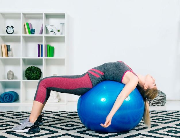 カーペットの上の青いピラティスボールで寝ている疲れ若い女性 無料写真