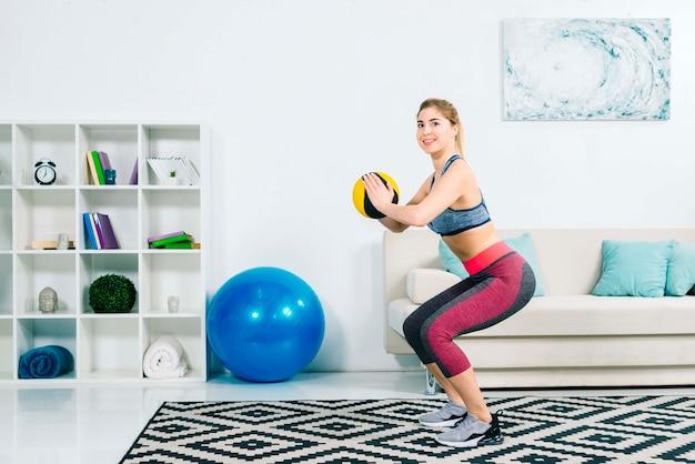 フィットネス若い女性が自宅のジムで医療ボール運動 無料写真
