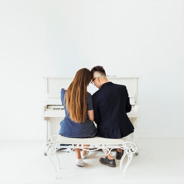 白い壁にピアノの前に座っている若いカップルの背面図 無料写真