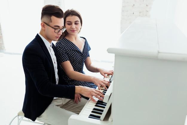 ピアノを弾いてハンサムな男を見て女性のクローズアップ 無料写真