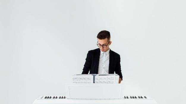 ハンサムな若い男が白い背景に対してピアノを弾く 無料写真