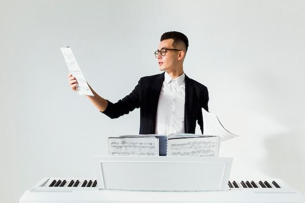 若い男が白い背景に対してピアノの後ろに立っている楽譜を読む 無料写真