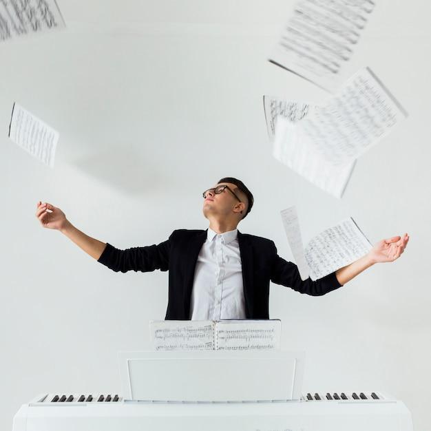 白い背景に対して座っている空気で楽譜を投げるピアノ奏者の肖像画 無料写真