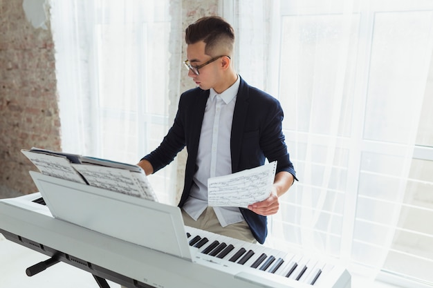 窓のそばに座ってピアノを弾く楽譜を保持している若い男 無料写真