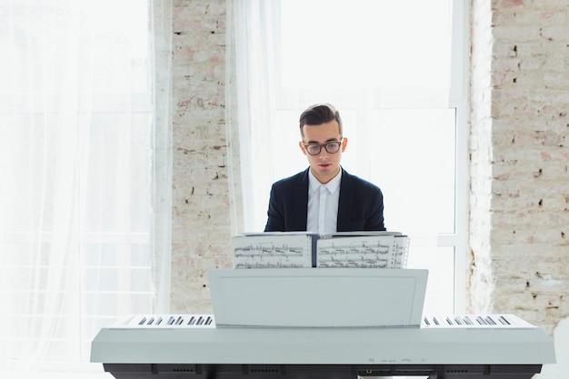 窓の前に座っているピアノを弾く若い男の肖像 無料写真