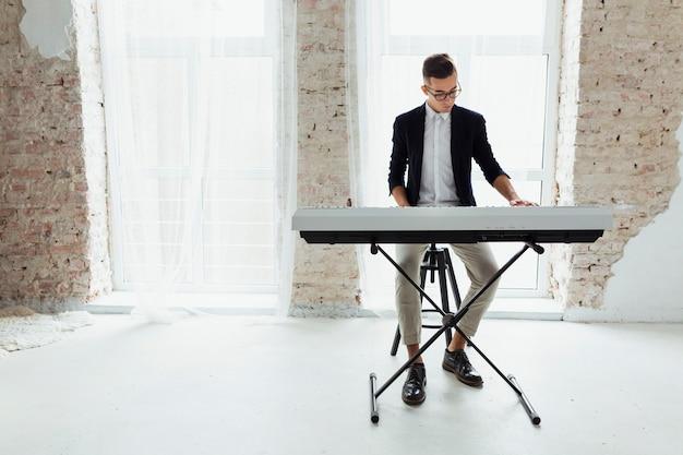 Привлекательный молодой человек играет на пианино, сидя у окна с белым занавесом Бесплатные Фотографии