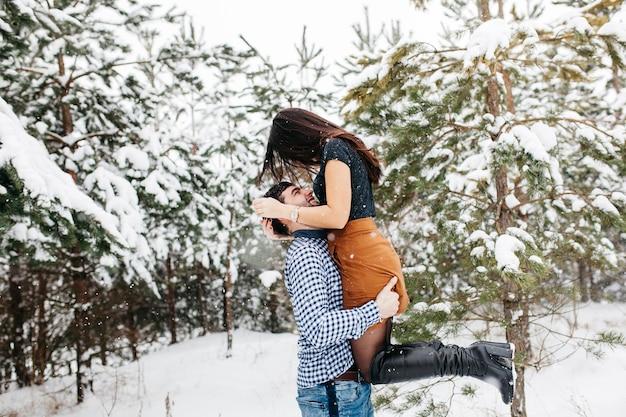 Мужчина держит женщину на руках в зимнем лесу Бесплатные Фотографии