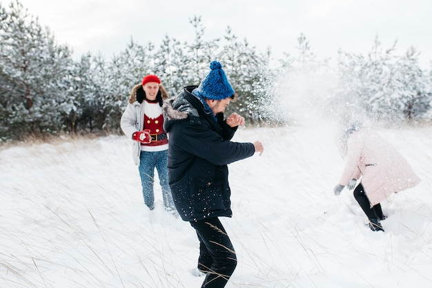Друзья играют в снежки в зимнем лесу Бесплатные Фотографии