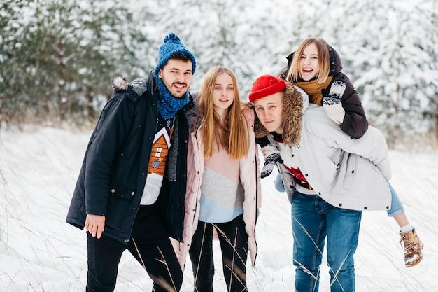 Радостные друзья стоят в зимнем лесу Бесплатные Фотографии