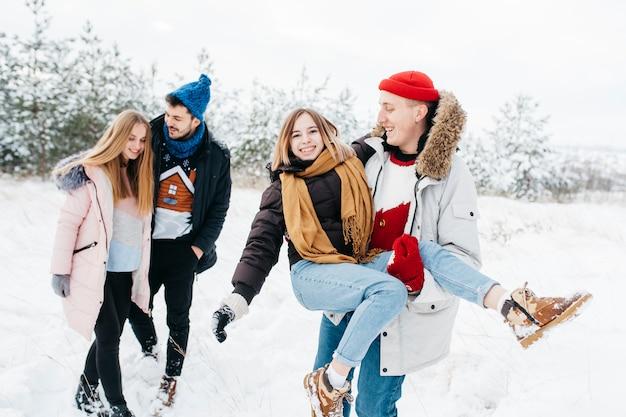Молодые пары веселятся в зимнем лесу Бесплатные Фотографии