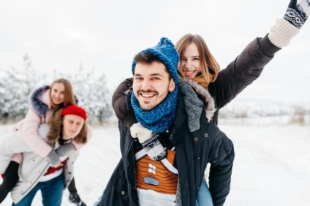 冬の森の背中に女性を運ぶ男 無料写真