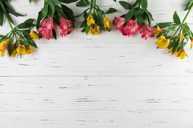 白い木製の織り目加工の背景にアルストロメリアの花の花束 無料写真