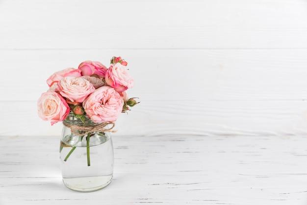 白い木製の織り目加工の背景にガラスの瓶にピンクのバラの花 無料写真