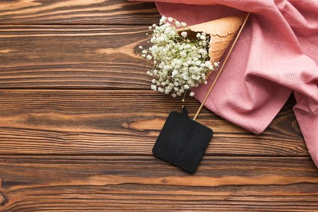 黒のスピーチの小道具と木製の織り目加工の背景にピンクの織物のアイスクリームコーンの中の石膏 無料写真