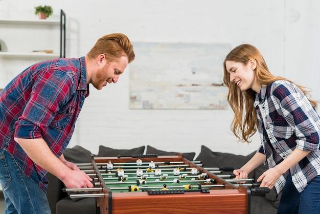 テーブルサッカーで遊んで楽しんで笑顔金髪の若いカップル 無料写真