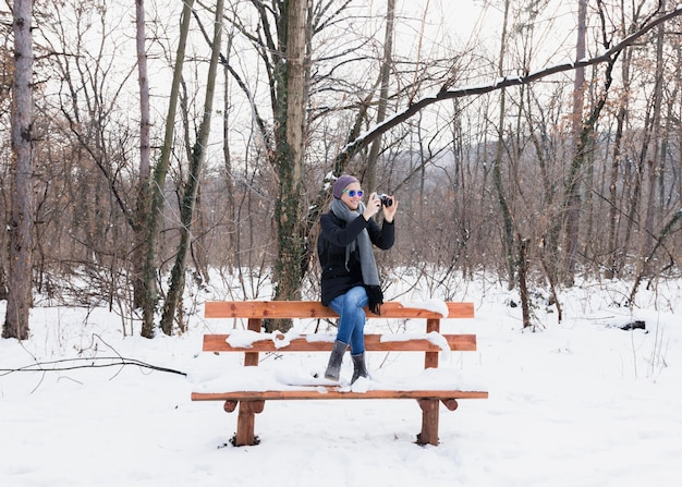 雪の中でベンチに座っている冬に写真を撮る若い女性の笑みを浮かべてください。 無料写真