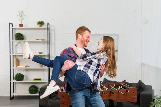 リビングルームのテーブルサッカーの前で彼女のガールフレンドを運ぶ笑顔の若い男 無料写真