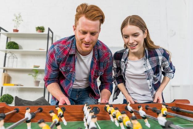 自宅でテーブルサッカーの試合をして笑顔の若いカップルのクローズアップ 無料写真