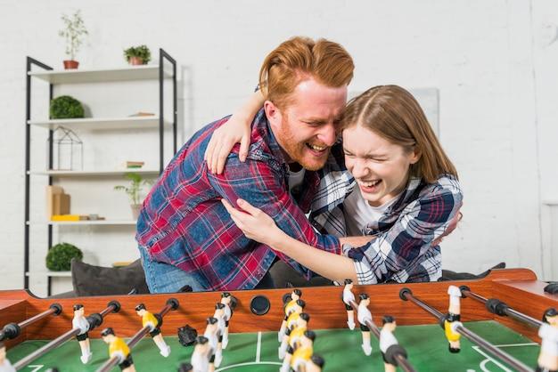 自宅でテーブルサッカーの試合の後ろに楽しんでいる若いカップル 無料写真