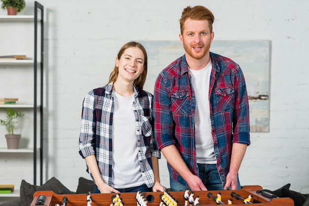 リビングルームでのテーブルサッカーの試合の後ろに立っている若いカップルの肖像画 無料写真