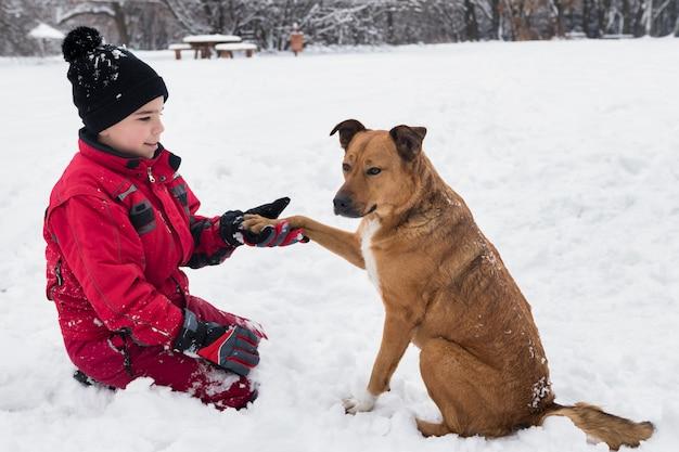 Улыбающийся мальчик держит собачью лапу в зимний сезон Бесплатные Фотографии