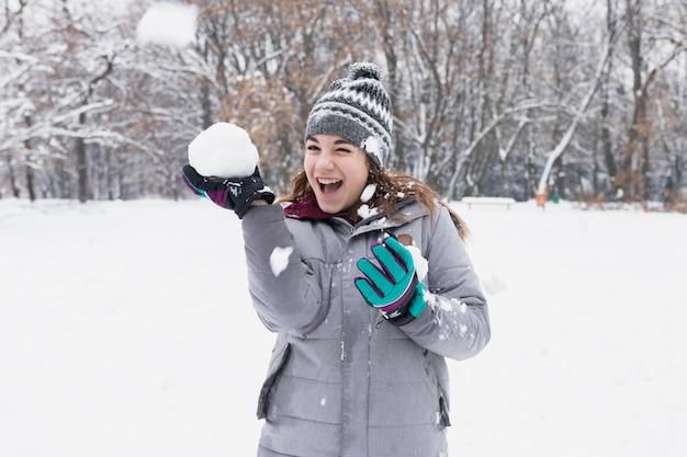 森の中の雪で遊んで幸せな女の子のクローズアップ 無料写真