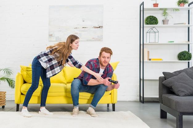 彼のボーイフレンドからビデオゲームをプレイする若い女性 無料写真