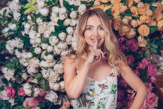 バラの背景の前に立っている静かなジェスチャーを作る若い女性の笑みを浮かべてください。 無料写真