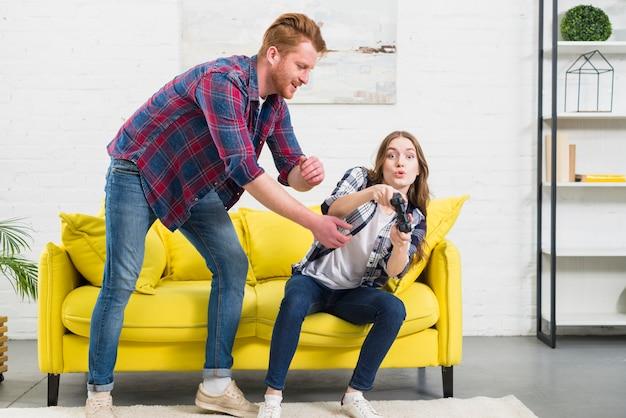自宅で彼のガールフレンドの手からジョイスティックを取ろうとしている若い男 無料写真