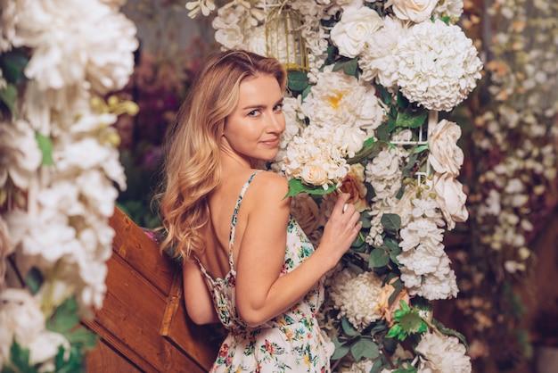 白い花の装飾の近くに立っている金髪の若い女性 無料写真