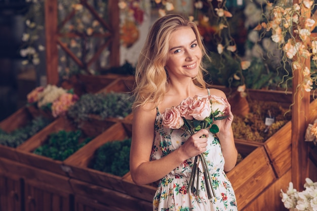 花屋で手に立っているピンクのバラを保持している金髪の若い女性 無料写真