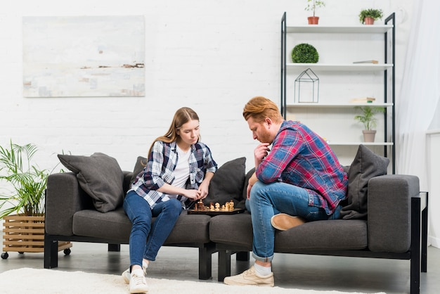 リビングルームでチェスのゲームをプレイソファーに座っていた若いカップル 無料写真